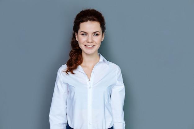 キャリアの成果。彼女のオフィスにいる間笑顔であなたを見ているうれしそうな素敵な魅力的な実業家