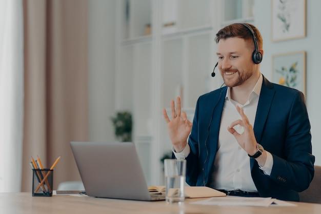 경력 및 거리 직업 개념입니다. 공식적으로 옷을 입은 수염을 기른 남성 기업 직원이 노트북 웹캠에서 확인 표시를 하고 데스크톱에서 온라인 통화 포즈를 위해 헤드셋을 사용하여 새로운 지식을 얻습니다.