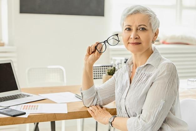 경력, 비즈니스 및 성공 개념. 노트북, 서류 및 책상에 계산기와 함께 그녀의 직장에 앉아, 안경을 들고, 휴식을 갖는 부드러운 회색 블라우스에 매력적인 좋은 찾고 사업가