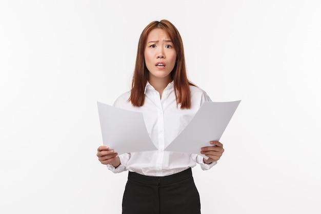 Концепция карьеры, бизнеса и женщин. взволнованная милая неуверенная молодая азиатская офисная леди имеет проблемы с бумагами, перепутанными документами и выглядящими обеспокоенными, держит бумаги с тревогой, уставившись