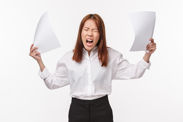 Career, business and women concept. portrait of distressed and annoyed aggressive young asian woman screaming pissed-off and angry, throwing documents, being outraged,