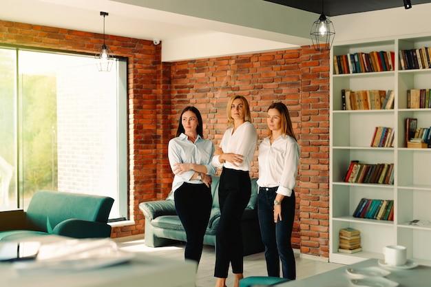 강한 힘든 찾고 현대 사무실에 서있는 팔을 교차 자신감을 보여주는 세 사람의 경력 비즈니스 여성 그룹. 성숙한 전문 비즈니스 아가씨 웃고.