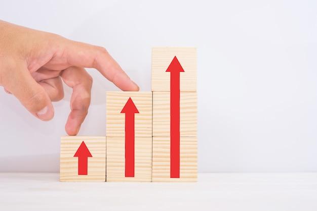 비즈니스 성장 성공 프로세스 개념을 위한 경력 사다리 경로입니다. 위쪽 화살표가 있는 계단식 계단 형태의 나무 블록에 대한 수동 단계