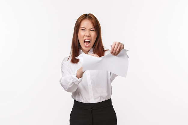 Career, office life and women concept. portrait of angry, pissed-off asian female ripping documents and screaming aggressive, grimacing bothered, feel distressed and upset,