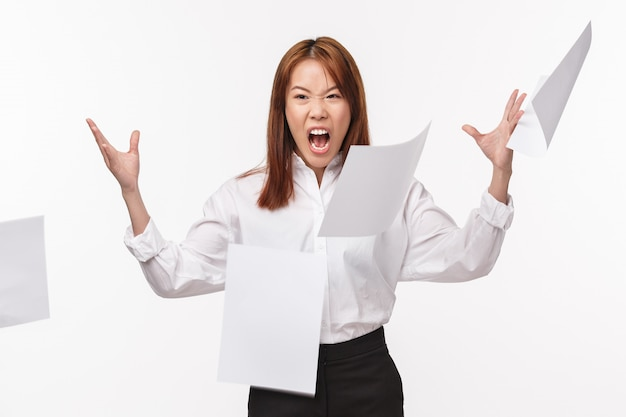 Career, office life and women concept. portrait of pissed-off hateful asian female in shirt, angry with bad paperwork, throwing papers, angry screaming and grimacing hateful,