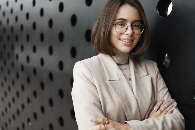 직업 기회, 여성 및 교육 개념. 기쁘게 자신감 표정, 크로스 손 가슴, 마른 사무실 벽으로 카메라를보고 세련 된 웃는 여자의 클로즈업 초상화.