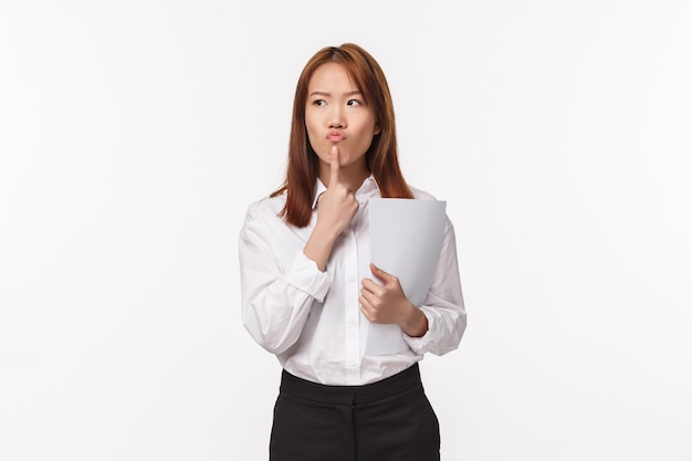 Career, profession and women concept. portrait of thoughtful asian woman thinking focused, look away pouting and touching lip pondering, hold documents, standing  on white wall