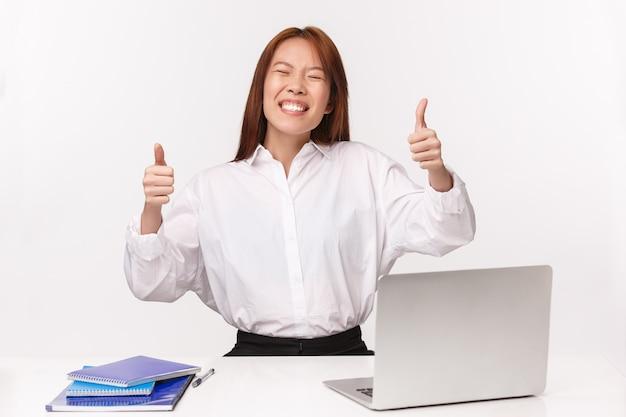 Карьера, работа и концепция женщин-предпринимателей. портрет конца-вверх удовлетворенной жизнерадостной азиатской дамы офиса усмехаясь счастливой, показывает похвалу больших пальцев руки вверх, хвастаясь достижением, проделанной работой