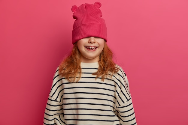 Carefree adorable girl plays indoor, enjoys great day, expresses positive attitude, hides face with hat, wears loose jumper with black stripes, poses against pink wall. children, fun concept