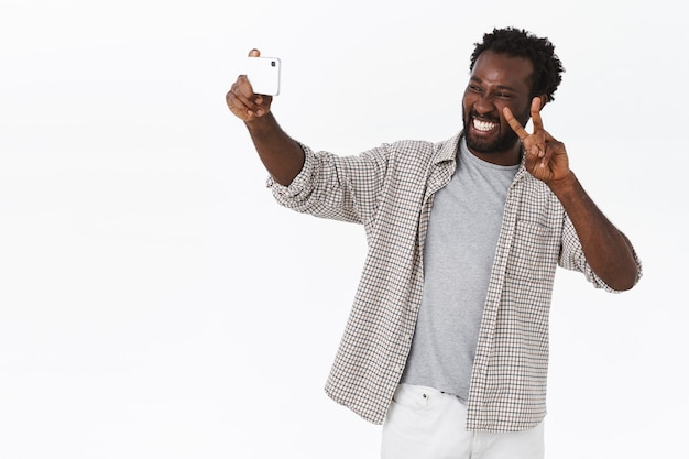 Il ragazzo barbuto afroamericano spensierato viaggia all'estero, facendo selfie durante le vacanze