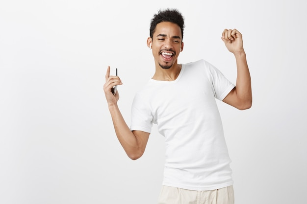 Carefree african american guy dancing and listening music in wireless earphones