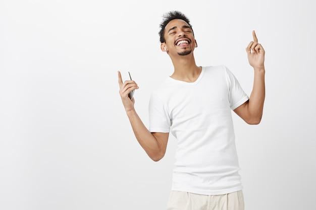 Ragazzo afroamericano spensierato ballare e ascoltare musica in auricolari wireless