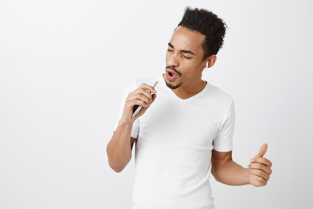 Carefree african-american guy playing karaoke, singing in smartphone mic, wearing wireless headphones