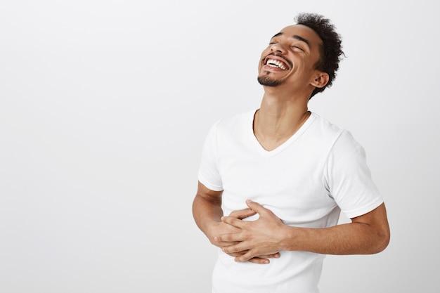 Беззаботный афро-американский мужчина смеется и улыбается, слышит смешную шутку