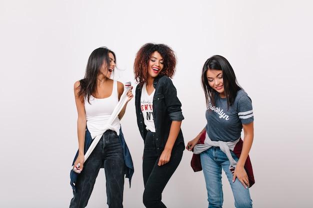Ragazza africana spensierata divertendosi con gli amici alla moda sorridenti. modello femminile nero emozionante che sta con gli occhi chiusi mentre le signore castane ballano accanto.