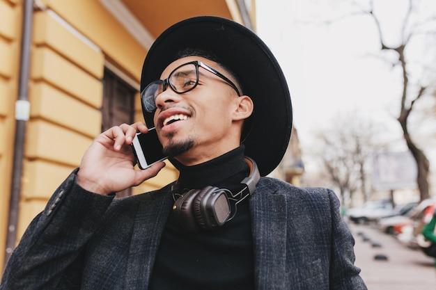 미소로 전화 통화하는 짧은 머리와 평온한 아프리카 남자. 셀과 거리를 걷고 모자에 열정적 인 흑인 젊은 남자의 야외 사진.