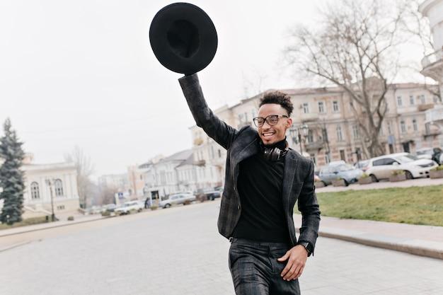 Беззаботный африканский мужчина с кудрявой прической танцует в парке под пасмурным небом. открытый портрет веселого парня-мулата, размахивающего шляпой с улыбкой.