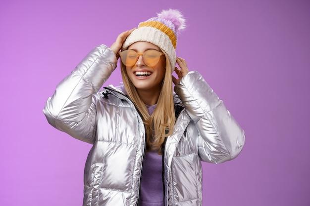 평온한 즐거운 매력적인 금발 여자 친구는 선글라스를 착용하고 멋진 화창한 겨울 날 스키 리조트 휴가를 즐기는 재미, 보라색 배경을 즐겁게 웃고 모자에 은색 세련된 재킷을 입혔습니다.