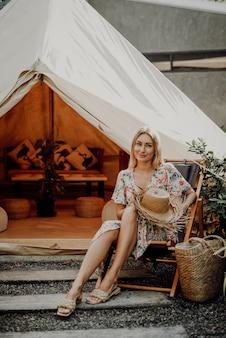 Беззаботная и радостная женщина-путешественница на отдыхе в таиланде позирует возле палатки, держащей соломенную шляпу и смотрящей в камеру.