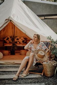 Беззаботная и веселая женщина-путешественница на отдыхе в таиланде позирует возле палатки, держа соломенную шляпу и глядя в сторону.