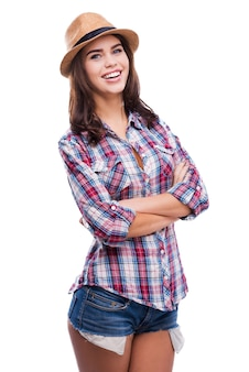 Беззаботный и позитивный. красивая молодая женщина в модной одежде, скрестив руки и глядя в камеру, стоя на белом фоне