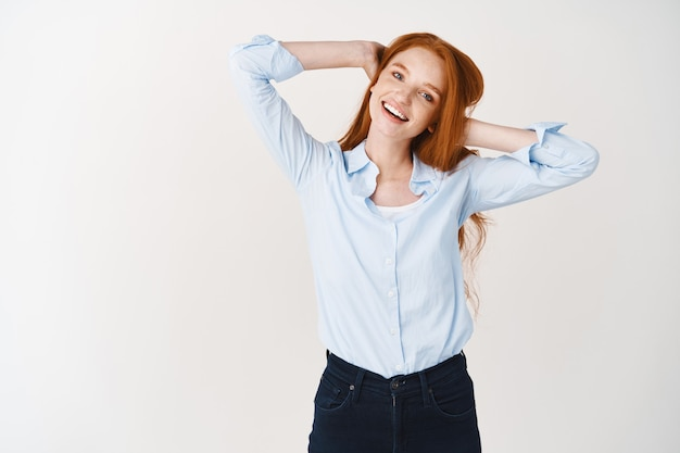 긴 빨간 머리를 가진 평온하고 편안한 여성, 머리에 손을 잡고 기쁨으로 웃고, 즐겁게, 흰 벽 위에 서서