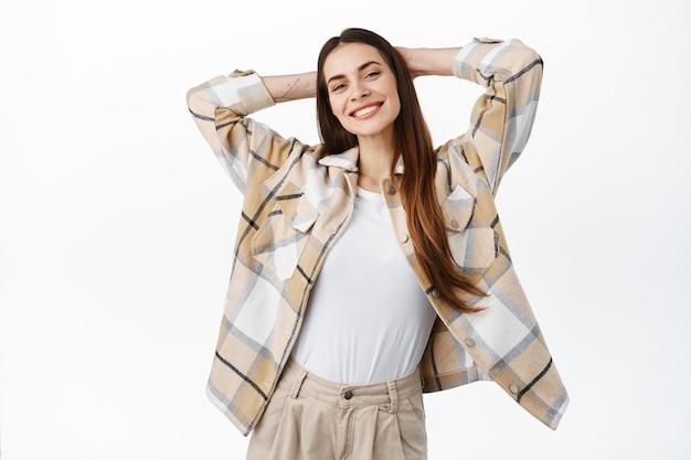 평온하고 편안한 젊은 여성은 머리 뒤로 손을 잡고 웃고, 여가 주말에 쉬고, 할 일이 없고, 게으른 날을 즐기고, 흰 벽에 행복하게 서 있습니다.