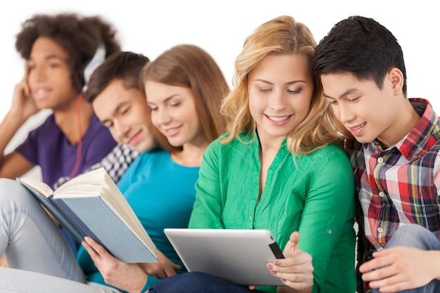 のんきで若い。白で孤立して座っている間一緒に時間を過ごす多民族の学生のグループ