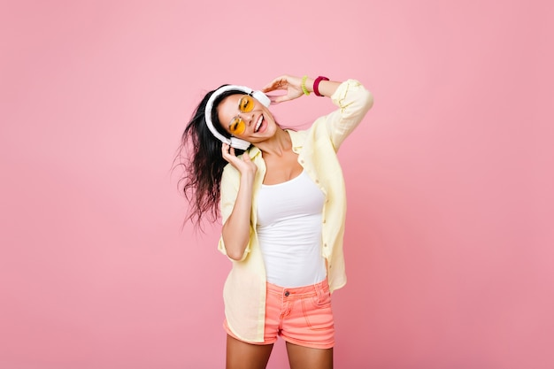 Carefree asian woman in summer clothes singing favorite song with happy face expression. indoor portrait of fascinating hispanic girl in yellow jacket having fun during dance.