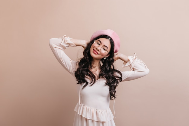 Carefree asian woman wearing french beret. positive long-haired chinese woman standing on beige background.