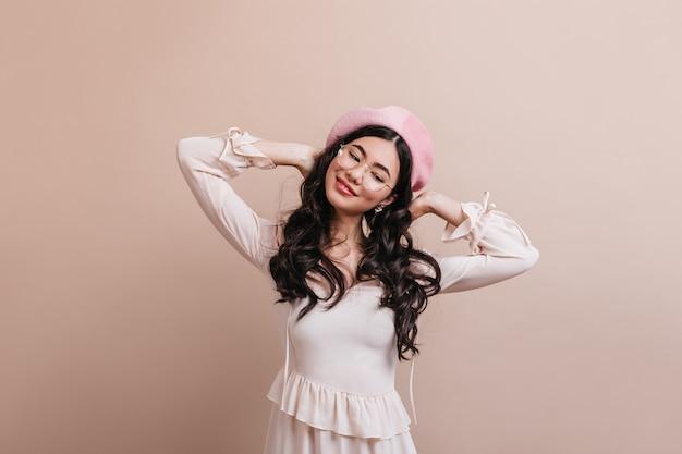 フランスのベレー帽を身に着けているのんきなアジアの女性。ベージュの背景に立っているポジティブな長髪の中国人女性。
