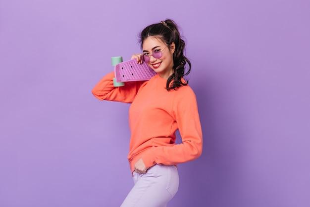 Беззаботная азиатская женщина с хвостиком, держащим скейтборд. студия выстрел из улыбающейся молодой женщины с longboard, изолированные на фиолетовом фоне.
