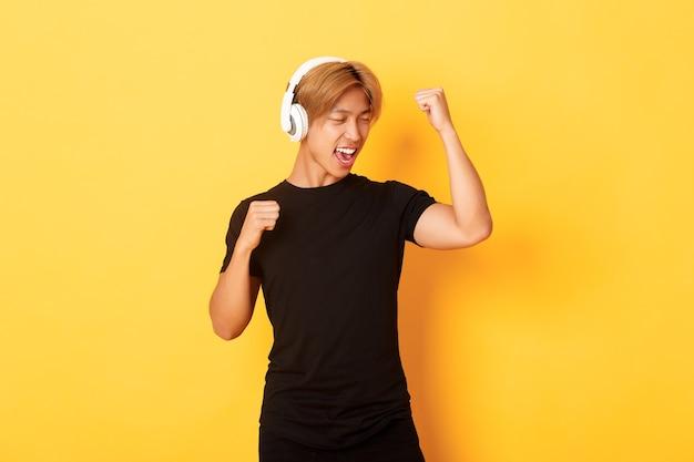 Беззаботный привлекательный азиатский парень со светлыми волосами, поет и танцует, как слушает музыку в беспроводных наушниках, стоя у желтой стены