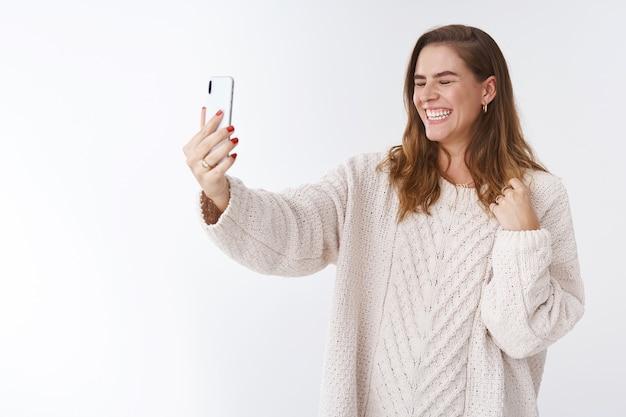 Spensierata attraente affascinante carismatica donna europea che ride ad alta voce facendo videochiamata estendere il braccio smartphone chiudere gli occhi ridacchiando felicemente parlando comunicare online via internet