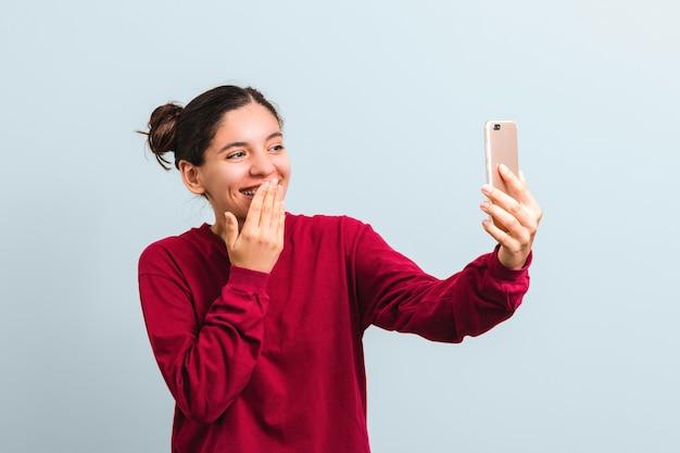 のんきな魅力的な魅力的なカリスマ的なヨーロッパの女性が大声で笑ってテレビ電話をかける