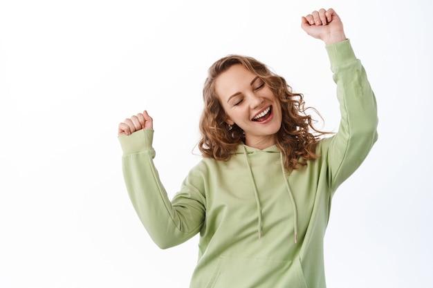 Ragazza attraente spensierata che balla, si diverte e si gode musica fresca, alzando le mani al ritmo della canzone, posando allegramente contro il muro bianco