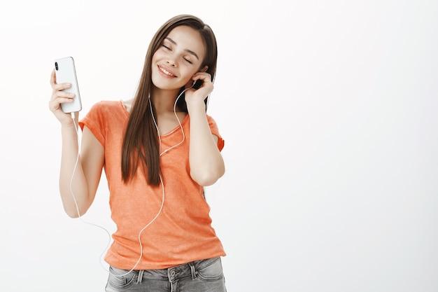 Беззаботная привлекательная девушка танцует с закрытыми глазами, слушает музыку на мобильном телефоне в наушниках
