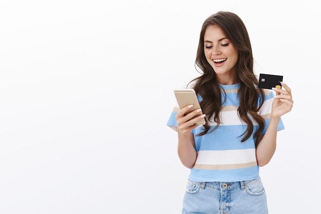 Беззаботная, привлекательная, гламурная, женственная женщина, делающая онлайн-заказ, оплачивающая покупки кредитной картой, довольная улыбающаяся, довольная, держащая смартфон, прокрутка интернет-магазина, вставка информации о банковском счете, белая стена
