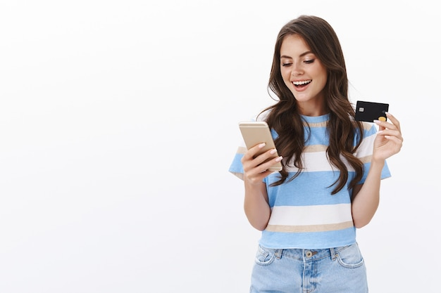 Carefree attractive glamour feminine woman making online order, paying with credit card for purchase, smiling pleased hold smartphone scroll e-shop, insert bank account info, white wall
