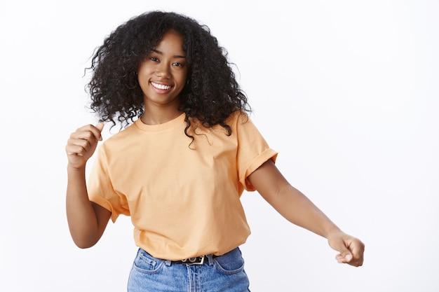 Spensierata attraente felice giovane ragazza afro-americana dai capelli ricci che indossa una maglietta arancione primaverile balla agitando le mani divertendosi godendo una festa fantastica sorridendo ampiamente, felice muro bianco