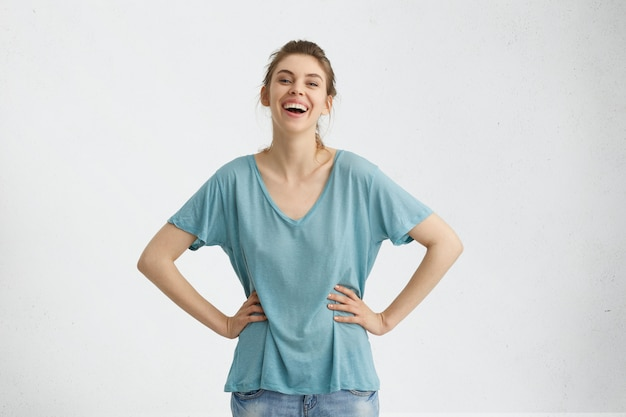 Donna snella attraente spensierata con capelli scuri, occhi azzurri che indossa jeans e maglietta blu allentata mantenendo le mani sulla vita sorridendo piacevolmente mentre posa contro il muro di cemento bianco