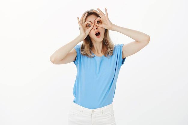 のんきな魅力的な女性が手眼鏡を作り、それらを通して見て、変な顔を作る
