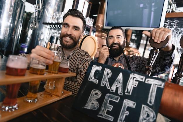 Carefree bearded bartenders in vintage style pub.