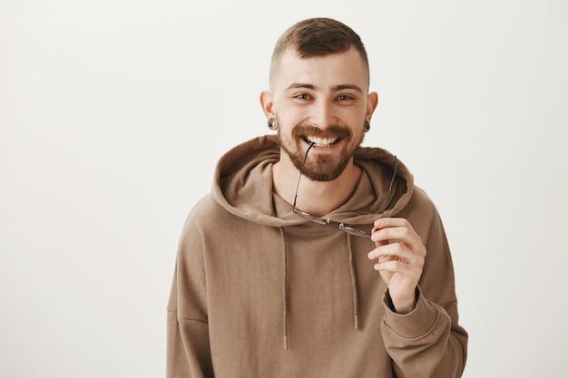 屈託のないひげを生やしたヒップスターの男が笑って幸せそうに見える