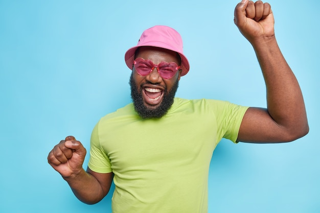 Carefree bearded man dances carefree keeps arms raised makes triumph dance wears pink hat sunglasses t shirt celebrates summer vacation isolated over blue wall