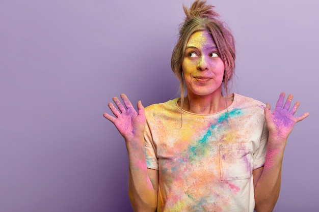 평온한 아름다운 여성 모델은 꿈꾸는 호기심 표정으로 옆으로 보이고 다채로운 분말로 얼룩진 손바닥을 들어 올리며 holi 축제 축하 행사에 참여하고 보라색 벽, 빈 공간 위에 서 있습니다.