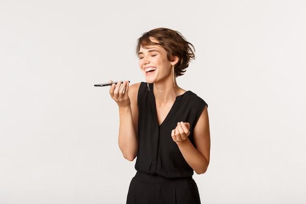 흰색 서 휴대 전화에 음성 메시지를 녹음하는 동안 웃 고 평온한 아름 다운 소녀.