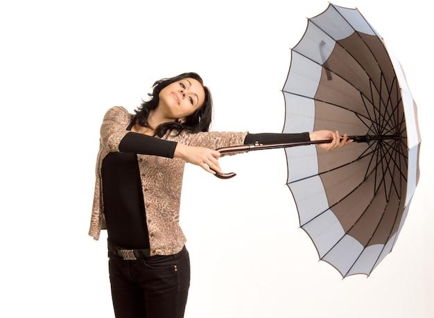 평온한 아름다운 트렌디 한 젊은 여성이 우산을 옆으로 들고 달리기