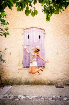 모자를 쓴 평온한 아름다운 여성이 질감이 있는 건물 벽의 오래된 나무 닫힌 창 앞에서 공중으로 점프합니다. 휴가 기간 동안 야외에서 공중에서 점프하는 황홀한 힙스터 여성