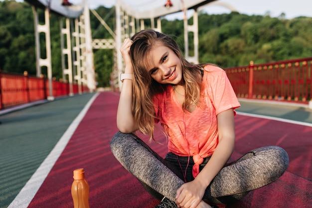 ジュースのボトルとスタジアムに座っているのんきなブロンドの女の子。トレーニング後に休んでいる魅力的な女性モデルの屋外の肖像画。
